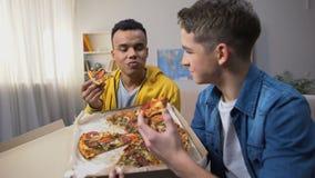享用比萨,不健康的食物的非裔美国人和欧洲少年朋友 股票视频
