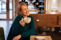 享用芬芳咖啡的年轻女人笑在咖啡馆 免版税库存照片