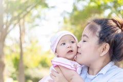 亲吻她的小婴孩的年轻美丽的亚裔母亲4个月女孩 家庭;有的母亲和的女儿放松的时间  图库摄影