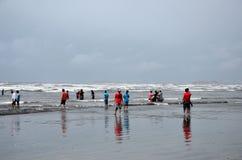 人们和家庭在水中趟过并且享用波浪在海视图海滩卡拉奇巴基斯坦 库存图片
