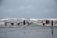 人们和家庭在水中趟过并且享用波浪在海视图海滩卡拉奇巴基斯坦 免版税库存图片