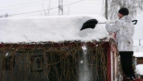 人从屋顶去除随风飘飞的雪 影视素材