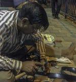 人修理在街道上的腰带 免版税库存图片