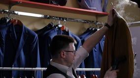 人卖主在服装商店剥去他的夹克,他为销售做准备 影视素材