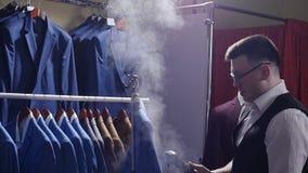 人卖主在服装商店剥去他的夹克,他为销售做准备 股票视频