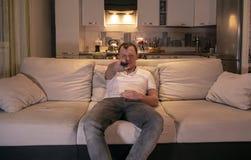 人在家坐一个沙发在与遥控的晚上在他的手上,看直接地照相机 免版税库存照片