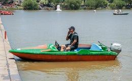 人在小船和谈话坐他的手机 库存图片