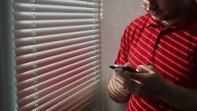 人在酒店房间和用途智能手机的窗口附近站立 股票视频