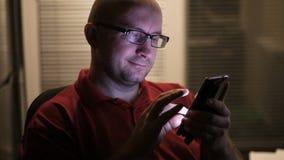 人在酒店房间和用途智能手机的窗口附近站立 股票录像