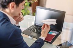 人商人在他的手上的举行一纸飞机origami 在网上购买的和预定的机票的概念 库存图片