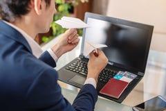 人商人在他的手上的举行一纸飞机origami 在网上购买的和预定的机票的概念 免版税库存图片
