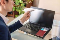 人商人在他的手上的举行一纸飞机origami 在网上购买的和预定的机票的概念 图库摄影