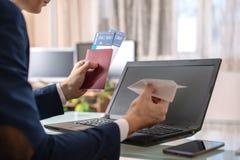 人商人在他的手上的举行一纸飞机origami 在网上购买的和预定的机票的概念 免版税库存照片