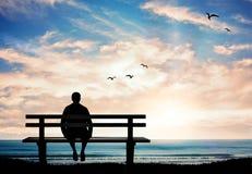 人剪影单独坐长凳在日落和认为 免版税图库摄影
