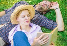 人和女孩在草阅读书放置 夫妇知己在浪漫日期 在爱的夫妇花费休闲看书  库存图片
