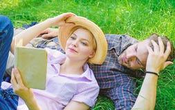 人和女孩在草阅读书放置 家庭享受休闲有诗歌或文学书草背景 夫妇 库存图片