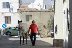 人和马在朗达街道上  库存图片