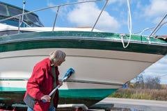 人清洁小船船身 免版税图库摄影