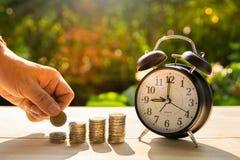 人抓住金钱硬币和硬币酒吧和闹钟在木桌上在阳光和迷离背景中提出储款硬币 库存图片