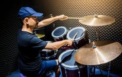 人投入了黑T恤杉对播放与木鼓槌的鼓集合在音乐屋子里 免版税库存照片