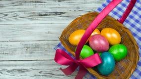 人投入桌复活节篮子用装饰的和色的鸡蛋,基督徒假日Pascha的概念或 股票录像