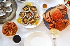人美好的用餐的海鲜和白酒在桌上 免版税库存图片