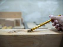人的手拿着胶浆的刷子在木粱 免版税库存照片