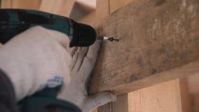 人的手运作的手套的从一个木板松开自动攻丝螺杆 拧紧在木的螺丝 影视素材