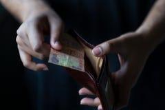 人的钱包在黑背景中 免版税图库摄影