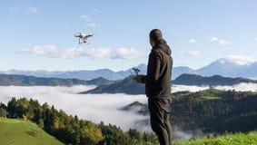 人运行的寄生虫飞行或盘旋由遥控与美好的有雾的风景在背景中 库存照片