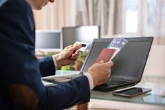 人藏品在互联网上的机票和借记卡购买使用膝上型计算机 在网上购买和预定 免版税库存图片