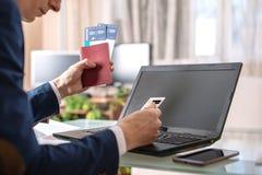 人藏品在互联网上的机票和借记卡购买使用膝上型计算机 在网上购买和预定 库存照片