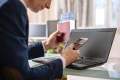 人藏品在互联网上的机票和护照购买使用膝上型计算机 在网上购买的和预定的票 免版税库存照片