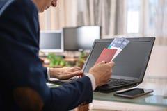 人藏品在互联网上的机票和护照购买使用膝上型计算机 在网上购买的和预定的票 免版税库存图片