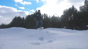 人脚在深刻的雪冬天进来 慢动作录影 有背包的人旅客在雪森林里走生活方式 股票视频