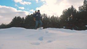 人脚在深刻的雪冬天进来 慢动作录影 有背包生活方式步行的人旅客在雪森林里 股票录像