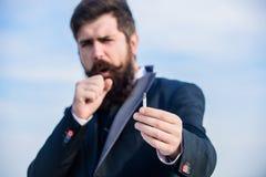 人香烟享受尼古丁影响 有胡子髭举行香烟的人 香烟帮助我们与一切从 免版税库存图片
