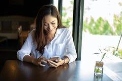 亚洲商人和妇女为通信使用机动性和接触智能手机并且检查商人在办公室 免版税库存图片