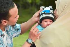 亚洲回教hijabi母亲和父亲步行通过公园有儿子的婴儿推车的,当他的妈妈照料她的todler时 免版税库存照片