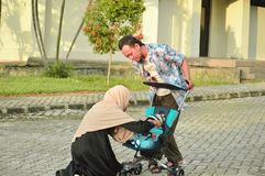 亚洲回教hijabi母亲和父亲步行通过公园有儿子的婴儿推车的,当他的妈妈照料她的todler时 库存照片