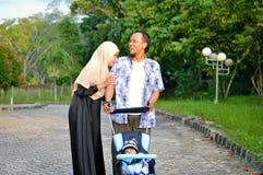 亚洲回教hijabi母亲和父亲步行通过公园有儿子的婴儿推车的,当他的妈妈照料她的todler时 免版税库存图片