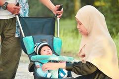 亚洲回教hijabi母亲和父亲步行通过公园有儿子的婴儿推车的 图库摄影