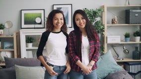 亚洲摆在为照相机的可爱的年轻女人和非裔美国人的朋友慢动作画象在家站立 股票视频