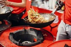 亚洲街道食物节日在城市 烹调面条和菜在一个平底锅的厨师在火 油煎的中国日本面条与 库存图片