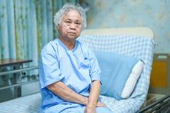 亚洲资深或年长老妇人妇女耐心的微笑明亮的面孔,当坐床在护理的医院时 免版税库存图片