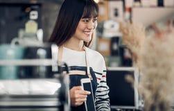 亚洲Barista侍者用途片剂接受从顾客在咖啡馆,咖啡馆所有者在逆酒吧,食物和饮料企业概念的命令, 免版税库存图片