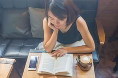 亚裔妇女读了一本书及时时间 免版税图库摄影