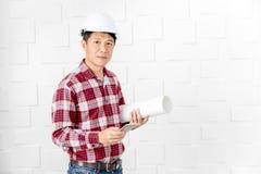 亚裔建筑师在工地工作办公室 库存照片