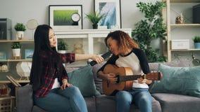 亚裔和非裔美国人的夫人在遥控在家放松弹吉他并且唱歌及时时间 股票录像