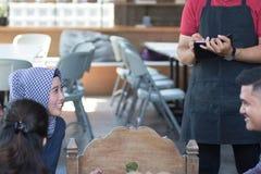 亚裔男性侍者写从costumers的命令在咖啡馆在背景 库存图片